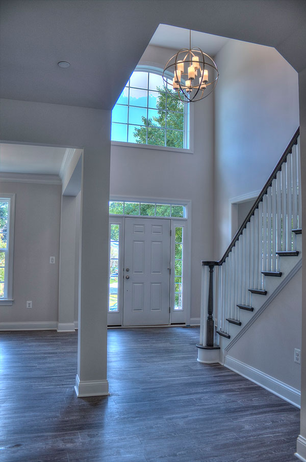 Looking into 2-story foyer from behind stairs