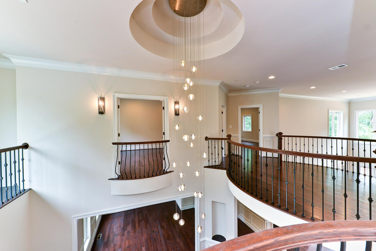 Foyer with elaborate circular tray ceiling, modern chandelier and romeo and juliet balconies